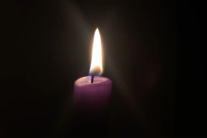 A candle burns in the darkness